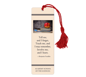 Tan laminated bookmark with red tassel with photo of books with apple on top and Benjamin Franklin quotation about learning